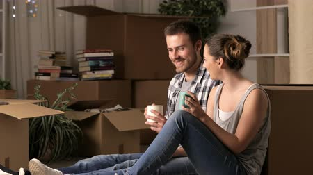 Couple talking about reforms and resting moving home in the night