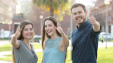 self motivated : Front view of three friends gesturing thumb up at camera in the street