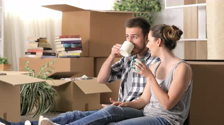 Happy couple moving home sitting on the floor