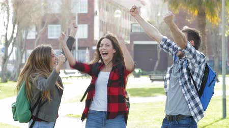 Three excited students jumping celebrating good news in a park 動画素材