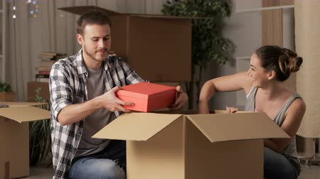 belongings : Happy couple moving house and joking unboxing belongings in the night