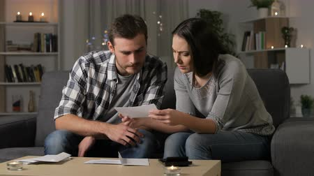 karartmak : Angry wife scolding her partner about expensive receipts sitting on a couch at home in the night Stok Video