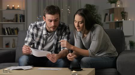 Preoccupied couple accounting checking receipts sitting on a couch in the night at home