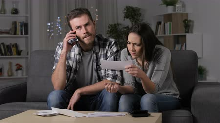 karartmak : Angry couple waiting for the phone to claim a wrong bank receipt in the night at home