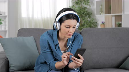 barganha : Amazed woman listening to music from smart phone sitting on a sofa at home Stock Footage