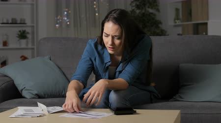 уведомление : Worried woman checking bank receipts on a couch at home in the night