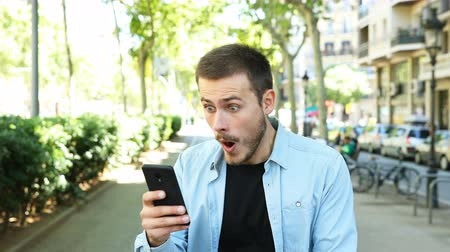 ortalama : Amazed man using smart phone and looks at camera in the street