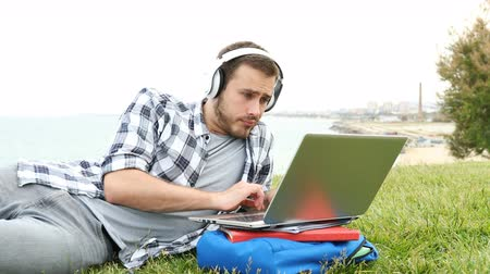 hiány : Bored and frustrated e-learning student using a laptop lying on the grass Stock mozgókép