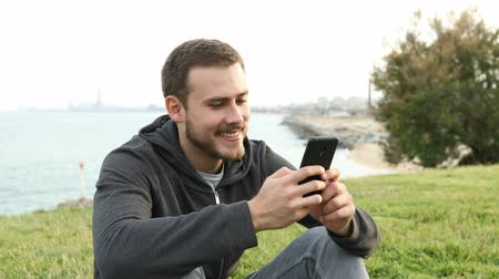 külvárosok : Happy teen texting on smart phone sitting on the grass in a coast city outskirts