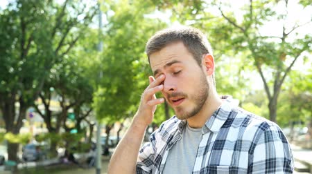 esfregar : Man rubbing his eyes that sting him due to allergy or infection in a park Stock Footage