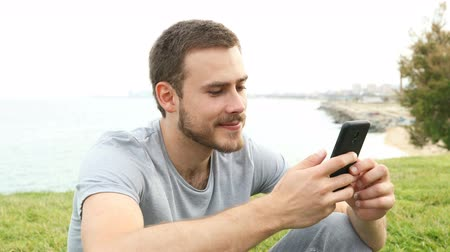 ortalama : Happy man texting on smart phone outdoors sitting on the grass Stok Video
