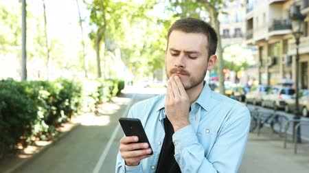 decidir : Doubtful man using smart phone trying to decide in the street Stock Footage