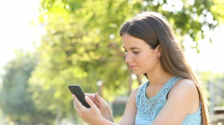 торг : Amazed woman finding awesome online smart phone content sitting in a park