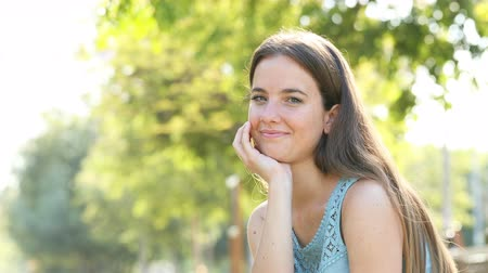 гордый : Smiley woman looking at camera sitting in a park