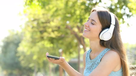 wearing earphones : Happy woman listening to music using headphones and smart phone in a green park Stock Footage