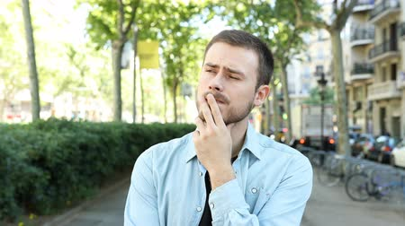 vélemény : Front view of a suspicious man listening to you doubting in the street