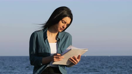 понимание : Concentrated woman studying reading notes on the beach