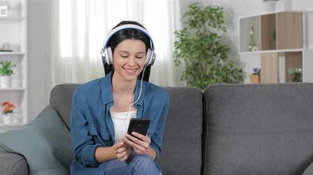 listens : Happy woman downloading and listening to music from smart phone sitting on a couch at home