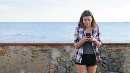 átlagos : Front view portrait of a happy teen texting on the phone walks towards camera