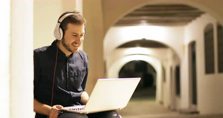 escuta : Happy man sitting on a laptop in the city Stock Footage