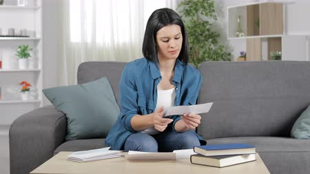 doubt : Confused woman reading a receipt at home sitting on a couch Stock Footage