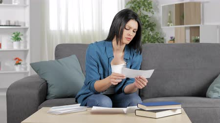 factuur : Angry woman reading a receipt sitting on a couch at home