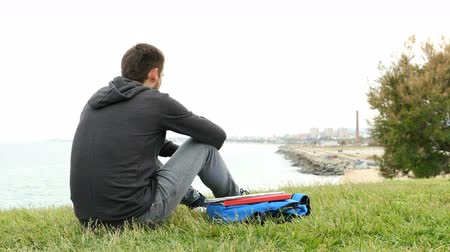 misunderstood : Sad student complaining on the grass looking at the city outskirts Stock Footage