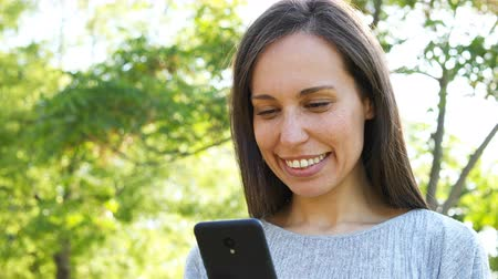 monouso : Close up of a happy adult woman using smart phone in a park