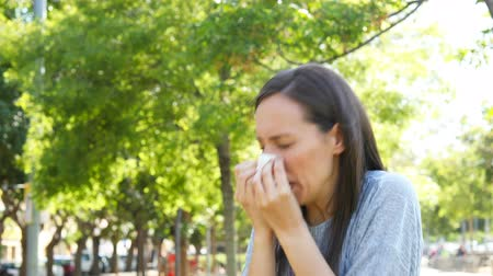 cubreboca : Ill woman sneezing and blowing on wipe standing outdoors in a park