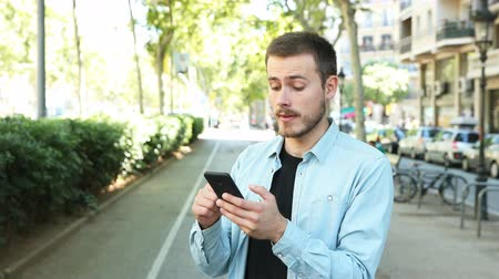 affirming : Man using smart phone and saying yes looking at camera in the street