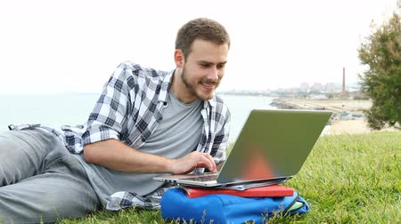 high school : Concentrated student browsing a laptop and learning lying on the grass