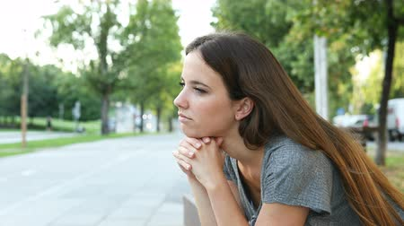 dubbioso : Serious pensive woman contemplating sitting on a bench in the street