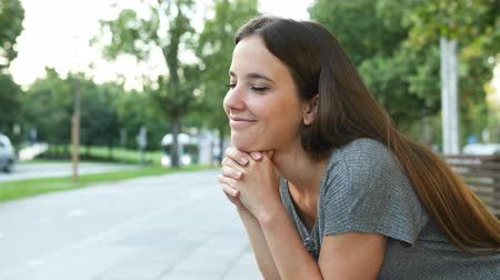 hopeful : Satisfied woman thinking looking away sitting on a bench in the street