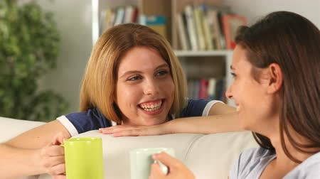 sharing : Happy teens talking and laughing drinking coffee sitting on a couch at home