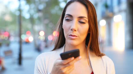 gebruiksaanwijzing : Front view of a woman using voice recognition on smart phone walking in the street at evening