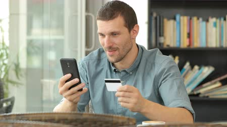 alku : Excited man buying online with credit card and smart phone in a coffee shop Stock mozgókép