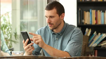 distraído : Serious man using a smart phone and finds funny content in a coffee shop