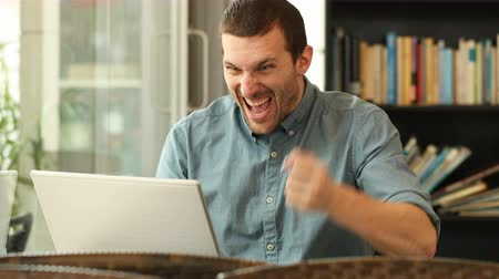 self promotion : Excited man using a laptop celebrating good news sitting in a coffee shop
