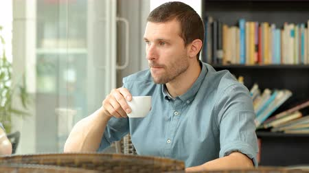 pensamento : Serious man drinking coffee and looking away in a restaurant