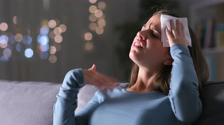 teplota : Stressed woman suffering heat stroke sweating and drying with a tissue sitting on a couch
