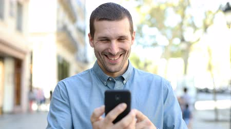 Front view portrait of a happy adult man walking towards camera using smart phone Stockvideo