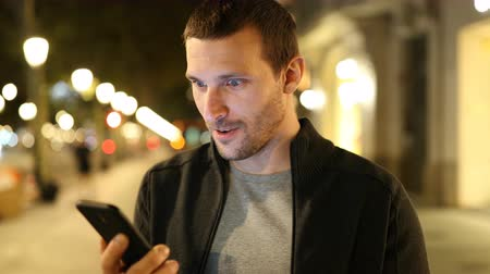 self promotion : Excited man checking smart phone online content standing in the street in the night Stock Footage
