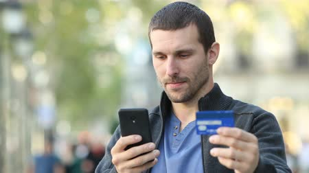 financiering : Serious adult man paying with credit card and mobile phone standing in the street