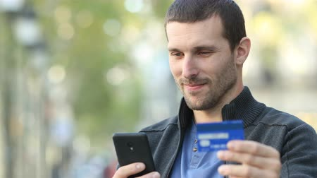 financiamento : Happy adult man paying with credit card and mobile phone standing in the street