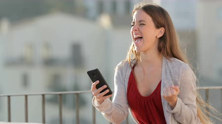 watching news : Excited woman checking mobile phone content celebrating success in a balcony a sunny
