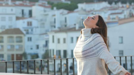 breathing fresh air : Relaxed woman breathing deeply fresh air standing in a balcony in winter Stock Footage