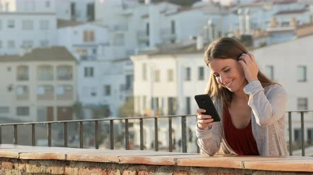 vendég : Happy woman using mobile phone in a balcony with copy space at side in a sunny day in Stock mozgókép