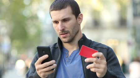 cancellation : Worried man buying on line with phone and credit card Stock Footage