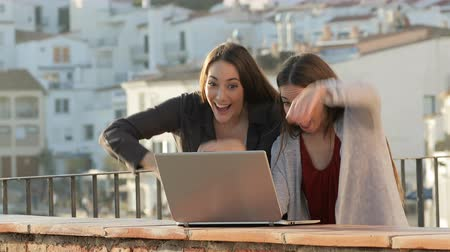 oportunidade : Two excited friends checking laptop celebrating success in a balcony in a rural Stock Footage