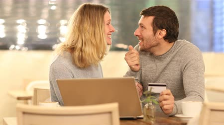 barganha : Front view of an excited couple buying online with laptop and credit card in a bar